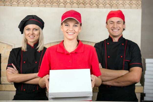 Mujer de entrega con cajas de pizza y dos chef feliz.