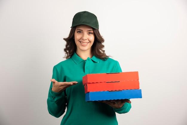 Mujer de entrega con cajas de pizza de pie en blanco.