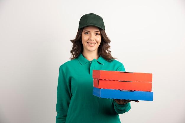 Mujer de entrega con cajas de pizza posando en blanco.