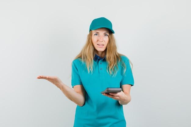 Mujer de entrega con calculadora con palma extendida en camiseta, gorra y mirando confundido