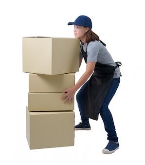 La mujer de la entrega en la camisa y el delantal grises está sosteniendo la camisa y el delantal aislados cajas. ella levantando cajas pesadas aisladas