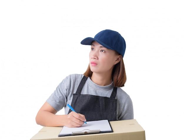 La mujer de entrega en camisa gris y delantal con pila de cajas lleva el paquete y presenta la forma de recepción aislada