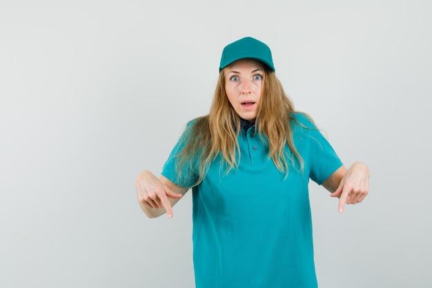 Mujer de entrega en camiseta, gorra apuntando hacia abajo y mirando sorprendido