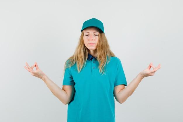 Mujer de entrega en camiseta, gorra haciendo meditación con los ojos cerrados y mirando tranquilo