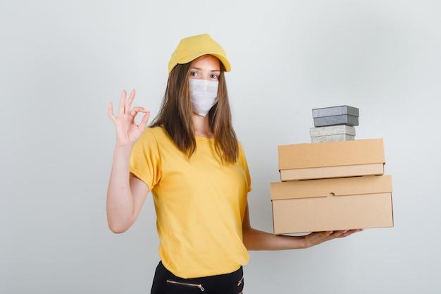 Mujer de entrega en camiseta, pantalón, gorra, máscara sosteniendo cajas con signo de ok y mirando alegre