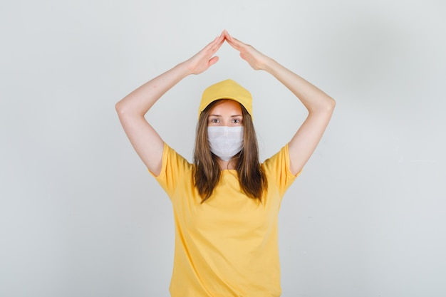 Mujer de entrega haciendo signo de techo de la casa por encima de la cabeza en camiseta, gorra, máscara y mirando contento