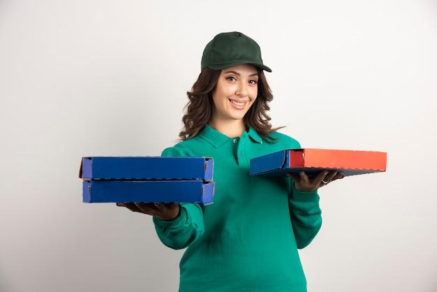 Mujer de entrega con montón de cajas de pizza.