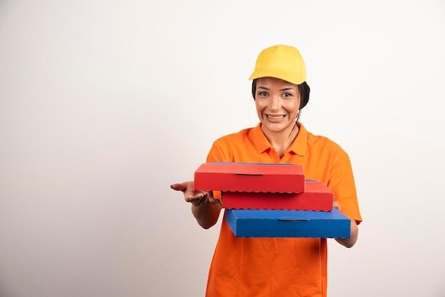 Mujer de entrega con montón de pizzas en la pared blanca.