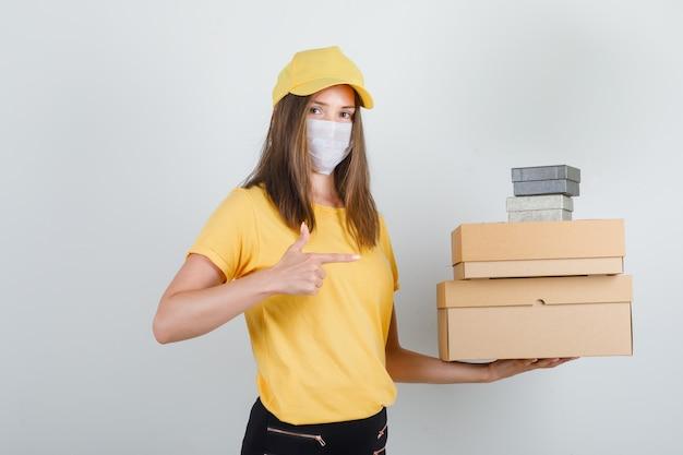 Mujer de entrega mostrando cajas con el dedo en camiseta, pantalón, gorra y máscara y mirando alegre