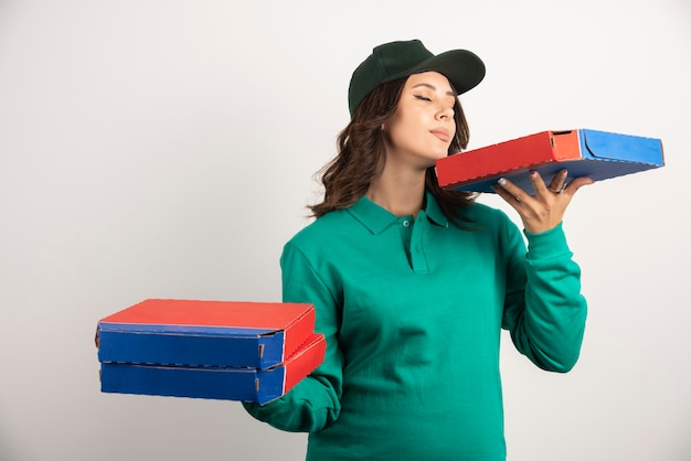 Mujer de entrega oliendo la caja de pizza.