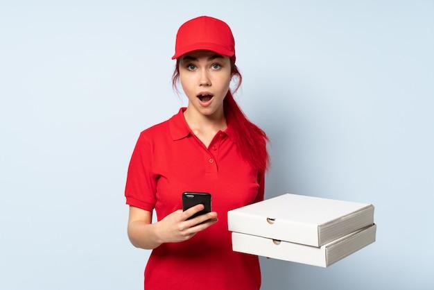 Mujer de entrega de pizza sosteniendo una pizza sobre pared aislada sorprendido y enviando un mensaje