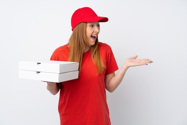 Mujer de entrega de pizza sosteniendo una pizza sobre pared rosa con expresión facial sorpresa