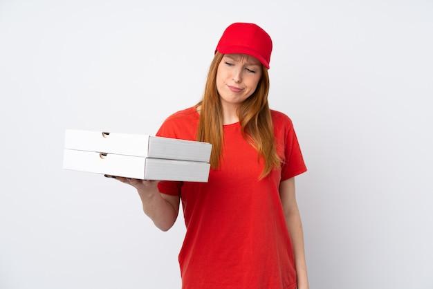 Mujer de entrega de pizza sosteniendo una pizza sobre pared rosa con expresión triste
