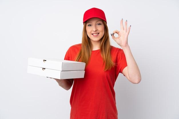Mujer de entrega de pizza sosteniendo una pizza sobre la pared rosa que muestra un cartel con los dedos