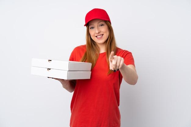 Mujer de entrega de pizza sosteniendo una pizza sobre la pared rosada te señala con una expresión segura