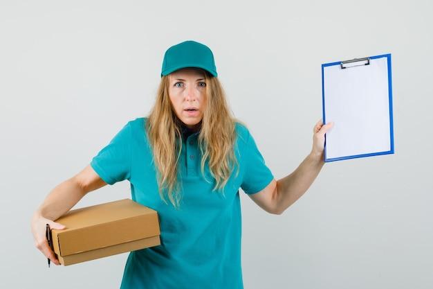 Mujer de entrega con portapapeles y caja de cartón en camiseta, gorra y mirando desconcertado.