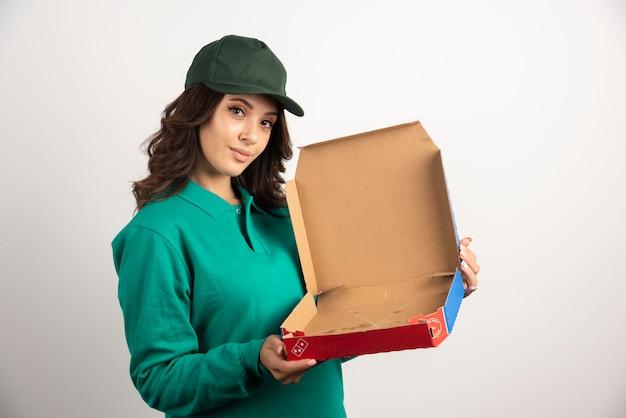 Mujer de entrega que muestra la caja de pizza vacía.