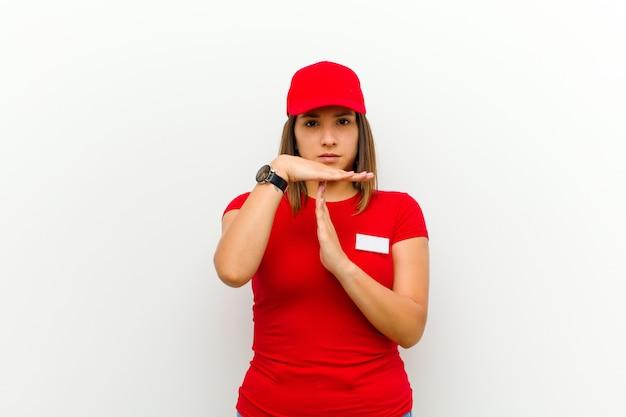 Mujer de entrega que parece seria, severa, enojada y disgustada, haciendo señal de tiempo de espera