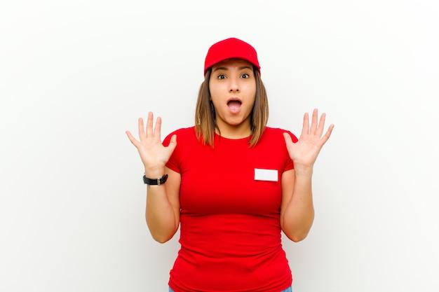 Mujer de entrega que parece sorprendida y asombrada con la boca abierta de sorpresa al darse cuenta de algo increíble