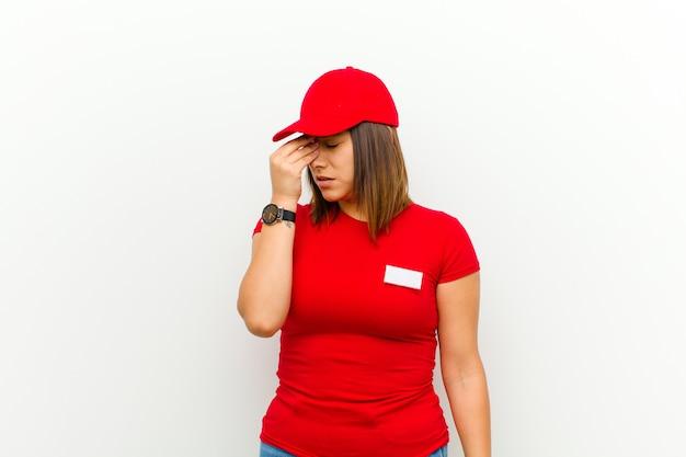Mujer de entrega que se siente estresada, infeliz y frustrada, toca la frente y sufre migraña de dolor de cabeza intenso