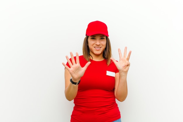 Mujer de entrega sonriendo y mirando amigable, mostrando el número nueve o noveno con la mano hacia adelante, cuenta atrás contra blanco