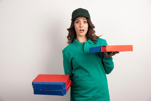 Mujer de entrega sorprendentemente mirando pizza.