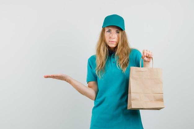 Mujer de entrega sosteniendo la bolsa de papel y extendiendo la palma a un lado en camiseta, gorra