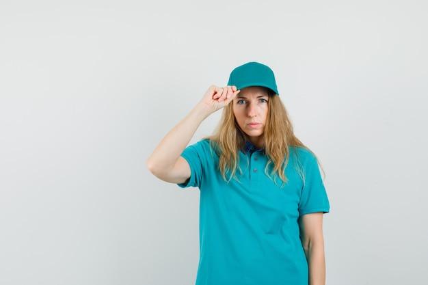 Mujer de entrega sosteniendo su gorra en camiseta, gorra y mirando seria