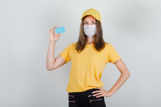 Mujer de entrega con tarjeta azul en camiseta, pantalón y gorra, máscara y mirando contento