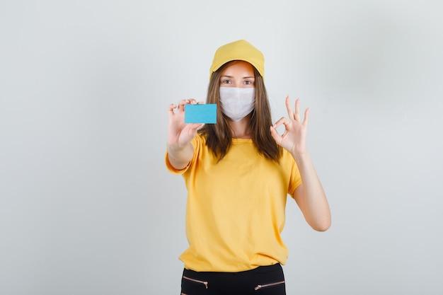 Mujer de entrega con tarjeta azul con signo ok en camiseta, pantalones y gorra, máscara y mirando contento