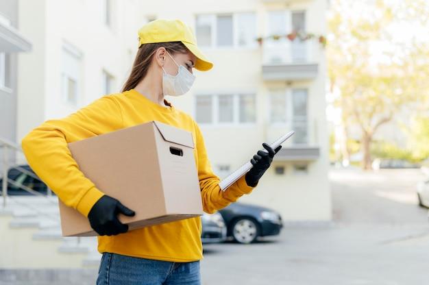 Mujer de entrega de tiro medio con caja