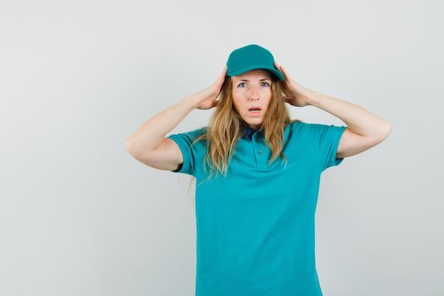 Mujer de entrega tomados de la mano a la cabeza en camiseta, gorra y mirando indefenso