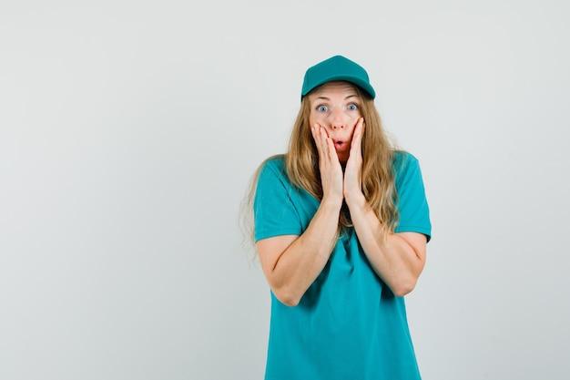 Mujer de entrega tomados de la mano cerca de la boca en camiseta, gorra y mirando sorprendido