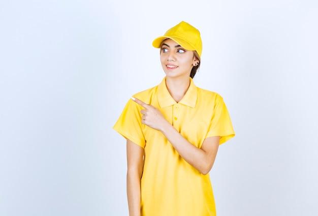 Mujer de entrega en uniforme amarillo de pie y apuntando hacia afuera con el dedo índice.