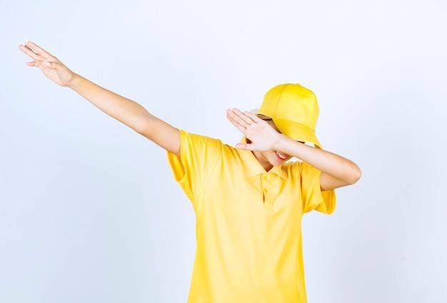Mujer de entrega en uniforme amarillo de pie y frotando.
