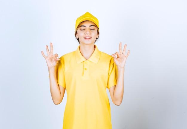 Mujer de entrega en uniforme amarillo de pie y meditando.