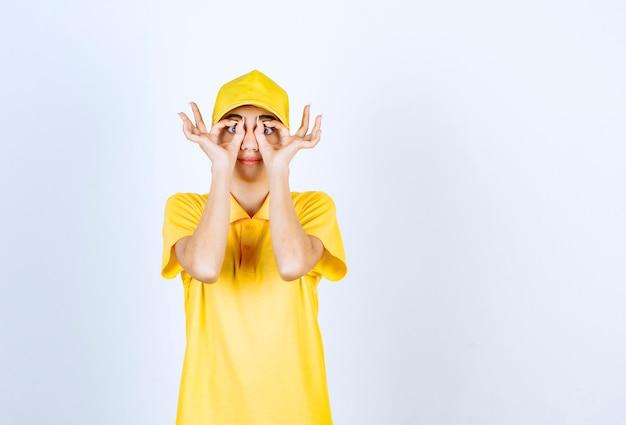 Mujer de entrega en uniforme amarillo de pie y mirando a través de las manos.