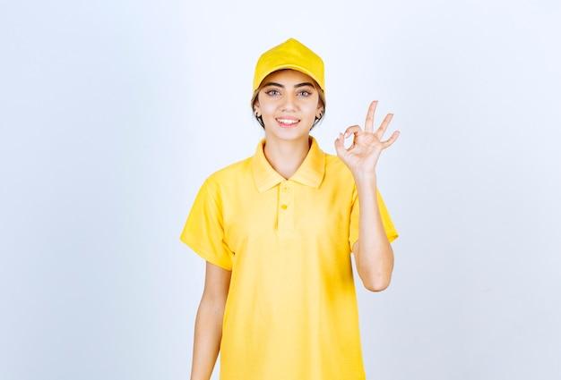 Mujer de entrega en uniforme amarillo de pie y mostrando gesto ok.