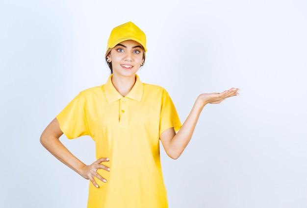 Mujer de entrega en uniforme amarillo de pie y mostrando la palma abierta.