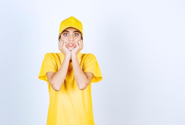 Mujer de entrega en uniforme amarillo de pie y posando.