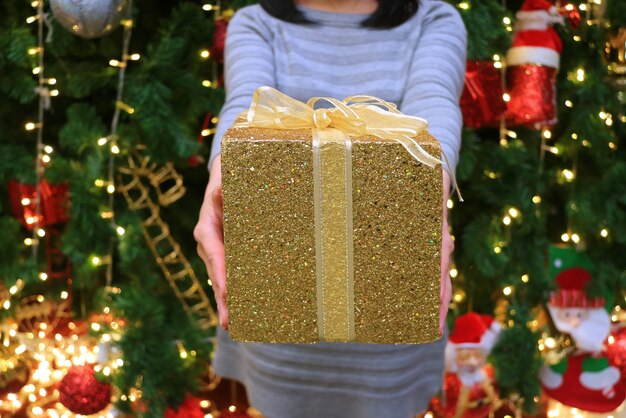 Mujer entregando una caja de regalo de brillo dorado a alguien borrosa árbol de navidad
