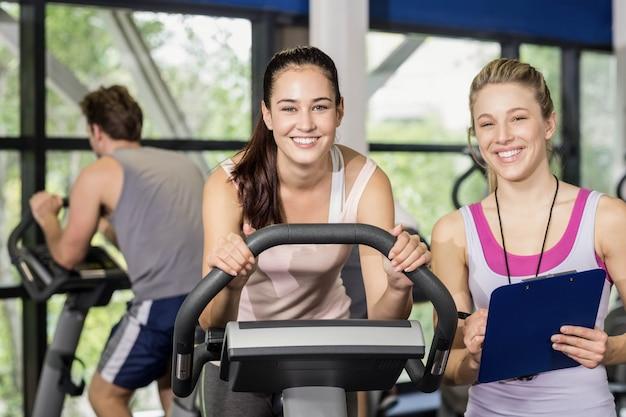Mujer de entrenador hablando con una mujer haciendo bicicleta de ejercicio en el gimnasio