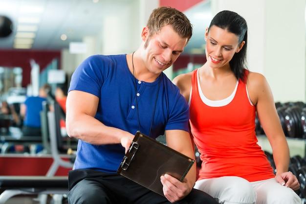 Mujer y entrenador personal en gimnasio con pesas