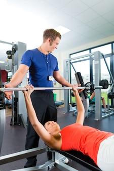 Mujer y entrenador personal en gimnasio