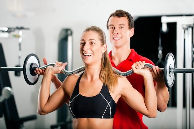 Mujer con entrenador personal en gimnasio