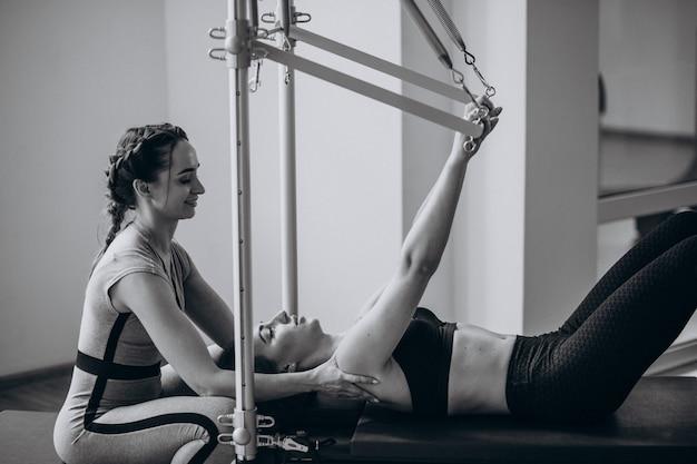 Mujer con entrenador de pilates practicando pilates
