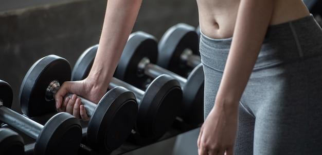 Mujer de entrenamiento con levantamiento de pesas para la construcción de cuerpo delgado y cuerpo delgado.