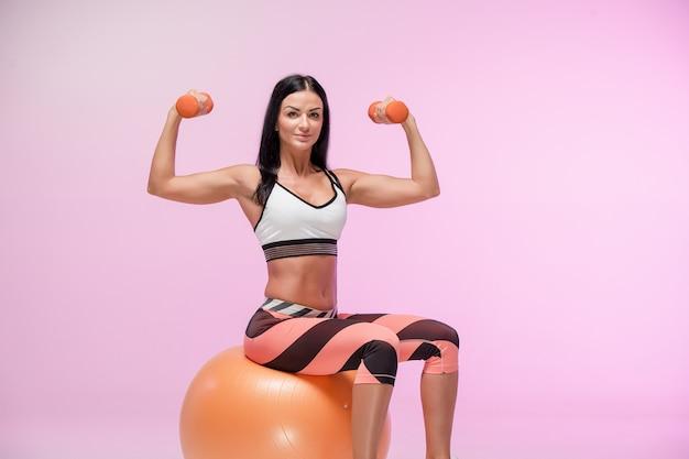 La mujer entrenando contra estudio rosa