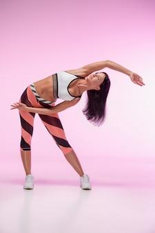 La mujer entrenando contra rosa