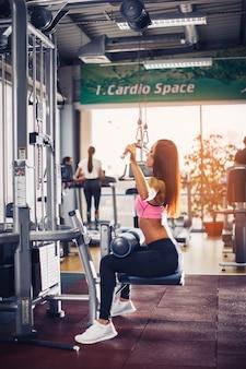 Mujer entrenando con máquina de levantamiento de pesas